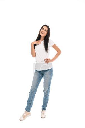 glückliche Frau, die mit der Hand in der Hüfte isoliert auf weiß steht