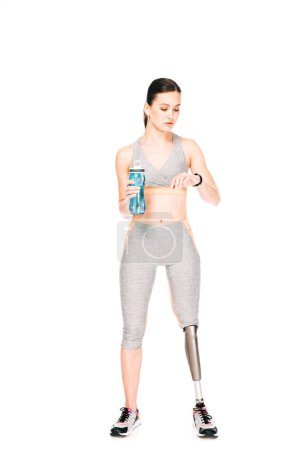 Photo for Full length view of sportswoman with prosthetic leg holding sport bottle and looking at smartwatch isolated on white - Royalty Free Image