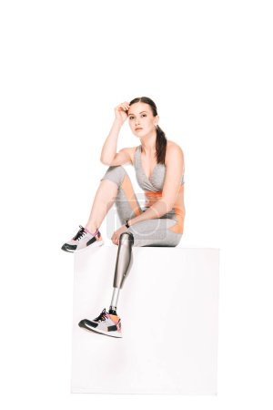 Photo for Disabled sportswoman with prosthetic leg sitting isolated on white - Royalty Free Image