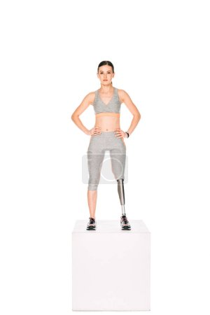 Photo for Full length view of disabled sportswoman with prosthetic leg standing with hands on hips isolated on white - Royalty Free Image
