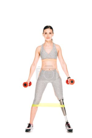 full length view of disabled sportswoman with resistance band and dumbbells isolated on white