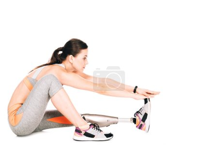 Photo for Side view of disabled sportswoman with prosthesis stretching isolated on white - Royalty Free Image