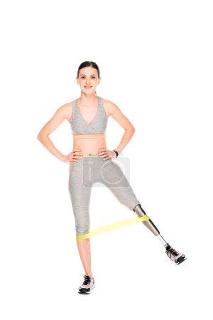 Photo pour Vue pleine longueur d'une sportive handicapée souriante avec prothèse avec bande de résistance isolée sur blanc - image libre de droit