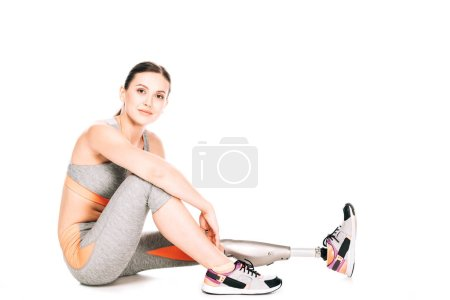 Photo for Smiling disabled sportswoman with prosthesis sitting on white - Royalty Free Image