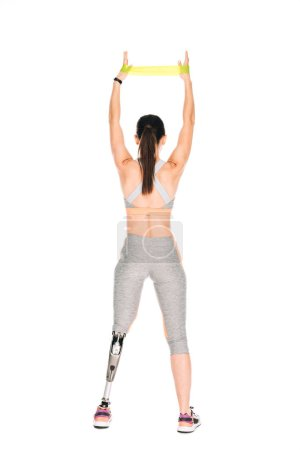 Photo pour Back view of disabled sportswoman with prosthesis training with resistance band isolated on white - image libre de droit