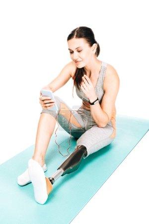 Behinderte Sportlerin sitzt auf Fitnessmatte und hört Musik in Kopfhörern isoliert auf weißem Untergrund