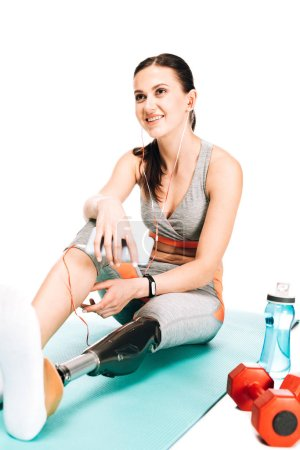 Photo pour Sportif handicapé assis sur tapis de fitness et écouter de la musique dans des écouteurs isolés sur blanc - image libre de droit