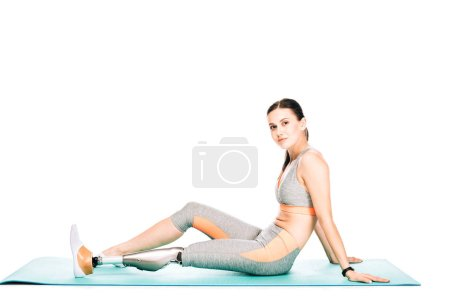 Photo for Disabled woman in sportswear sitting on fitness mat isolated on white - Royalty Free Image