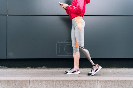 partial view of disabled sportswoman with prosthesis holding smartphone on street
