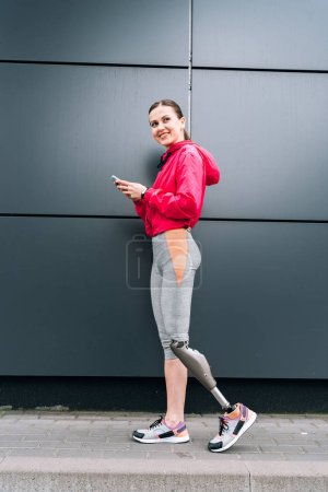 Photo pour Vue pleine longueur d'une sportive handicapée souriante avec prothèse à l'aide d'un smartphone dans la rue - image libre de droit
