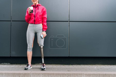 cropped view of smiling disabled sportswoman holding cup and smartphone on street