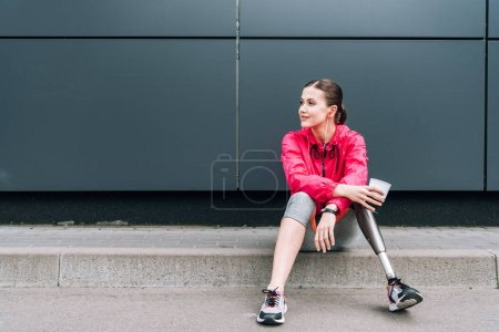 Photo for Disabled sportswoman listening music in earphones and holding cup on street - Royalty Free Image