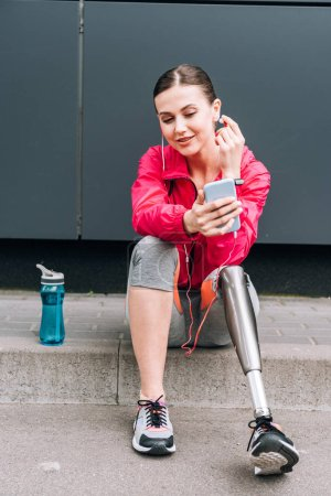 smiling disabled sportswoman listening music in earphones on street