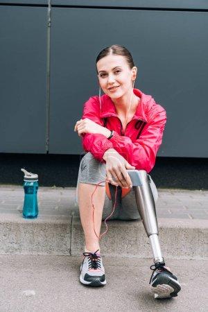 Photo pour Sportive handicapée souriante écoutant de la musique dans les écouteurs de la rue - image libre de droit