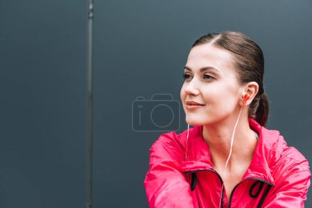 Photo for Dreamy young woman listening music in earphones on street - Royalty Free Image