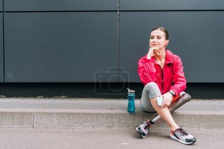 disabled sportswoman listening music in earphones on street