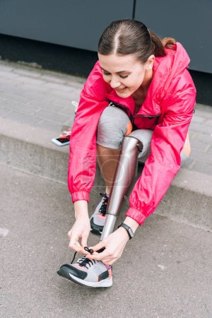 smiling disabled sportswoman with prosthesis tying shoelace on street