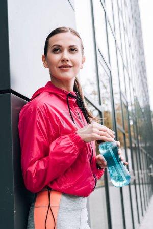 Photo pour Sourire belle sportive tenant bouteille de sport dans la rue - image libre de droit