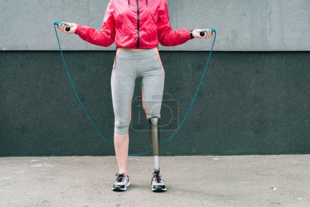 partial view of disabled sportswoman with skipping rope on street