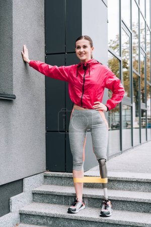 Photo pour Vue pleine longueur d'une sportive handicapée souriante s'entraînant avec une bande de résistance dans la rue - image libre de droit