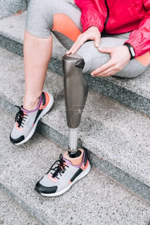 Photo for Partial view of disabled sportswoman with prosthesis sitting on stairs - Royalty Free Image