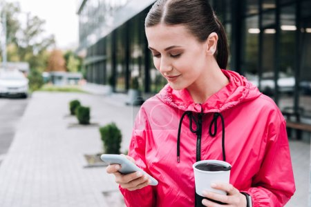 smiling sportswoman holding cup and using smartphone on street