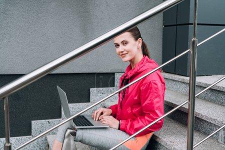 sportif handicapé souriant utilisant un ordinateur portable tout en étant assis sur les escaliers dans la rue