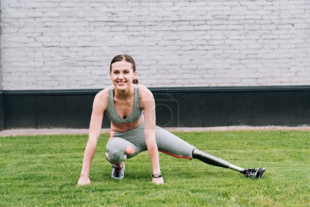 Photo for Smiling disabled sportswoman with prosthesis stretching on grass - Royalty Free Image