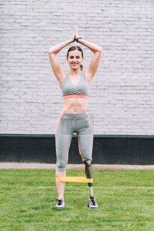 Photo pour Vue pleine longueur d'entraînement sportif handicapé souriant avec bande de résistance sur herbe - image libre de droit