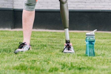 vue partielle de la sportive handicapée debout près de la bouteille de sport sur l'herbe dans la rue