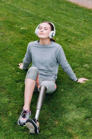 sportif handicapé assis sur l'herbe et écouter de la musique dans les écouteurs