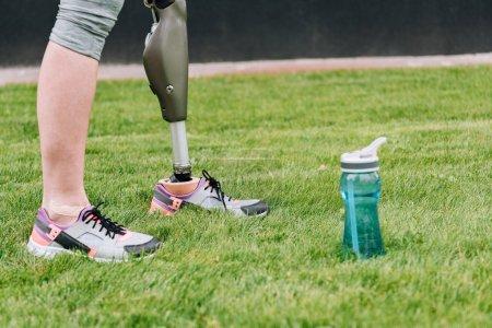 Photo pour Vue partielle de la sportive handicapée debout près de la bouteille de sport sur l'herbe - image libre de droit