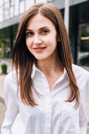 Photo pour Attrayant jeune femme en chemise blanche souriant sur la rue - image libre de droit