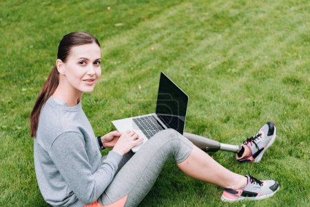 Photo for Disabled sportswoman using laptop with blank screen while sitting on grass - Royalty Free Image