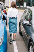 back view of disabled woman in denim skirt near cars on street