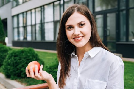 Photo for Smiling attractive young woman holding apple on street - Royalty Free Image