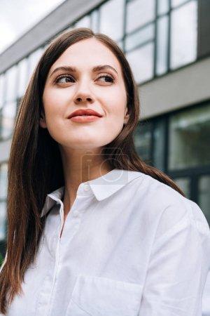 jolie jeune femme souriante en chemise blanche sur la rue