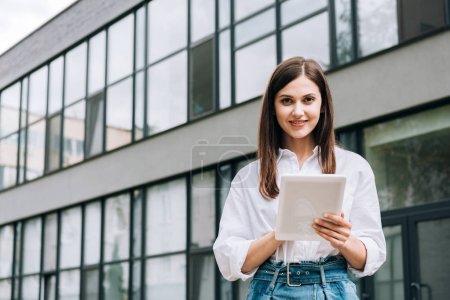 mujer joven sonriente en camisa blanca usando tableta digital en la calle