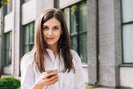 Photo pour Jeune femme souriante en chemise blanche tenant smartphone et écoutant de la musique dans les écouteurs dans la rue - image libre de droit