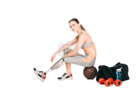 smiling disabled sportswoman sitting on basketball ball isolated on white