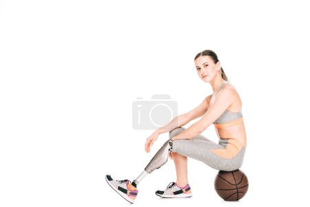 disabled sportswoman sitting on basketball ball isolated on white