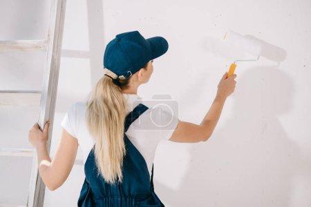 Photo pour Vue arrière du jeune peintre en uniforme debout près du mur blanc et tenant rouleau de peinture - image libre de droit