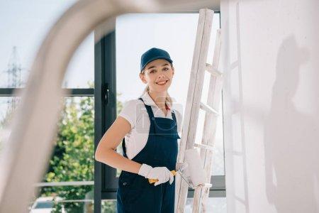 Photo pour Foyer sélectif de jolie jeune peintre en uniforme tenant le rouleau à peindre et souriant à la caméra - image libre de droit