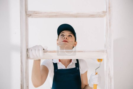 Photo pour Pretty young painter in uniform looking up while climbing on ladder - image libre de droit