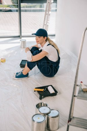 Photo for Beautiful young painter in overalls and cap sitting on floor near paint roller in roller tray and cans with paint - Royalty Free Image