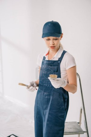 Photo pour Beautiful young painter in overalls and cap holding paintbrushes - image libre de droit