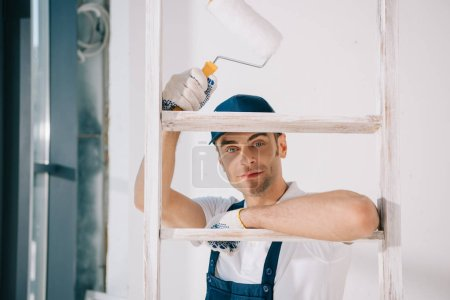 Photo pour Handsome young painter in uniform standing near ladder, holding paint roller and smiling at camera - image libre de droit