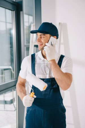 Photo pour Handsome young painter in uniform looking away while holding paint roller and talking on smartphone - image libre de droit