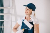"""Постер, картина, фотообои """"attractive young painter holding paint roller and talking on smartphone"""""""