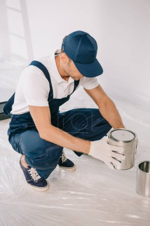 Photo pour Young painter in overalls and cap holding can with paint - image libre de droit